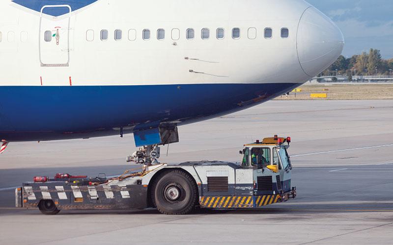 Flygplan transporteras av en traktor på marken.