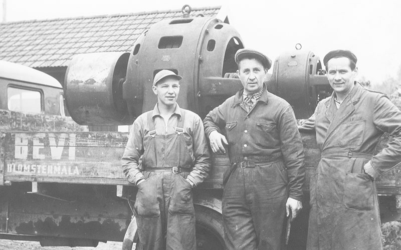 Three men in work clothes by a truck with a large electric motor on the flatbed, about 1940.